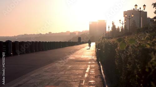 Canvas Print A man rides a bicycle along the promenade to meet the dawn