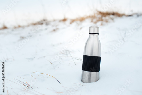 Obraz Close-up of steel reusable thermo water bottle in snow. - fototapety do salonu