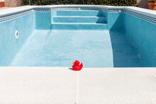 Red Rubber Duck At The Edge Of An Empty Swimming Pool