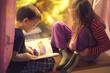 Dzieci czytają książkę przy oknie