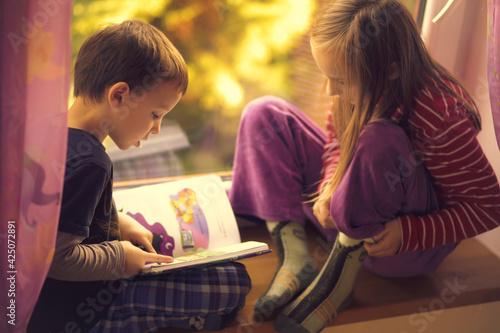 Obraz Dzieci czytają książkę przy oknie - fototapety do salonu