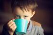 Chłopiec pije herbatę z kubka.