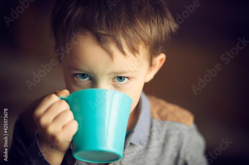 Fototapeta Chłopiec pije herbatę z kubka. obraz
