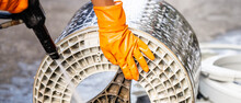 Person Hands Wearing Orange Gloves Holding Black High Pressure Spray Cleaning To Clean The Dirt At The Washing Drum.