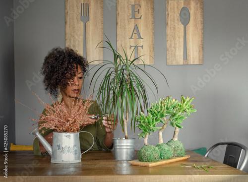 Black woman caring houseplants indoor.