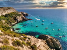 View Of A Beautiful Bay With Turquoise Water And Many Boats At Sunset