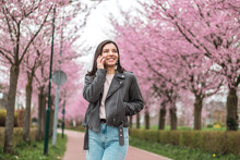Cheerful And Confident Young Woman Of Mixed Races Ethnicity On Phone With Beloved Friends Or Relatives Walking Alone In Bloomy Park With Pink Trees