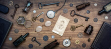 A Collection Of Antique Antiques Is Spread Out On The Table. Old Coins, Glasses, Photography, Glass Bottles, Keys, Watch And Compass. Vintage Collection.