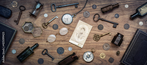 Fototapeta A collection of antique antiques is spread out on the table. Old coins, glasses, photography, glass bottles, keys, watch and compass. Vintage collection. obraz