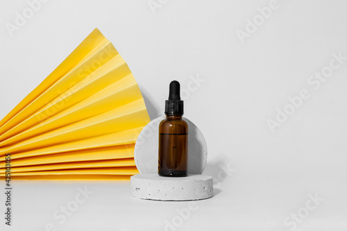 Brown dropper glass pipette bottle on gray concrete pedestal, yellow paper fan, white background, copy space. Serum, oil, acid. Zero waste glass container. Natural cosmetic. Spa, beauty, skincare - fototapety na wymiar