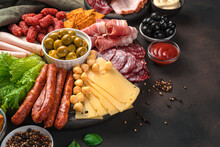 Sausages Of Different Types, Smoked Meat, Cheese And Olives On A Brown Background With Space To Copy. Charcuterie Board.