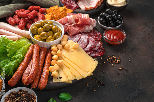 Fototapeta Sausages of different types, smoked meat, cheese and olives on a brown background with space to copy