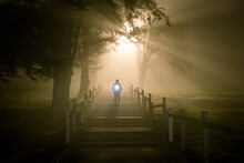 Silhouette Of Man Walking With A Torch In The Fog