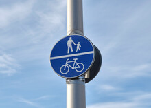 The Blue Sign People And Bicycles Allowed And The Sky In The Color