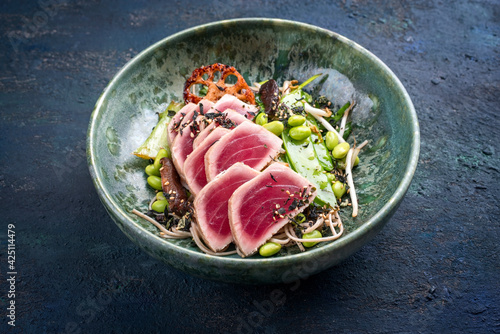 Modern style traditional Japanese gourmet seared tuna fish steak tataki with soba noodles and stir-fried vegetables served as close-up on a Nordic design bowl with copy space