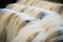 A Long Exposure Of Fast Moving Water In A Stepped Waterfall Or Weir From The Side, Concept Of Movement