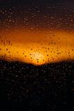 widok na zachód słońca zza zmoczonej szyby, krople wody w słońcu, romantyczny widok