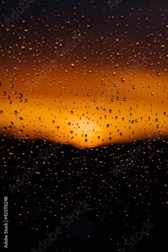 Fototapeta widok na zachód słońca zza zmoczonej szyby, krople wody w słońcu, romantyczny widok obraz