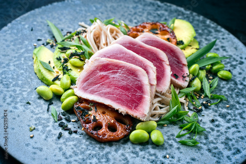 Modern style traditional Japanese gourmet seared tuna fish steak tataki with soba noodles and stir-fried vegetables served as close-up on a Nordic design plate with copy space