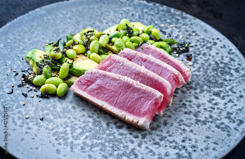 Modern style traditional Japanese gourmet seared tuna fish steak tataki with avocado fruit and edamame soy beans served as close-up on a Nordic design plate
