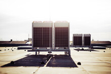 Air Vents On The Roof Of Building In Functional And Operational Condition. Sky Is Lit With Bright Light Made By Sun And Background Is Slightly Blurred. Focus Is On First Ventilation Unit In Front.