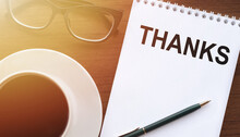 THANKS - Text On Paper With Cup Of Coffee And Glasses On Wooden Background In Sinlight.