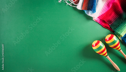 Fotografie, Obraz Cinco de Mayo holiday background made from maracas, mexican blanket stripes or poncho serape on green background