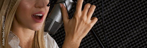 Cuadros en Lienzo Closeup caucasian female hand and mouth, singing in front of black soundproofing walls