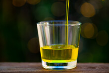 Pouring A Stream Of Yellow Oil Into A Clear Glass With A Light Effect Bokeh Background.