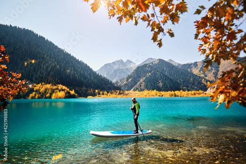 Obraz na plátne Man on stand up paddle board at mountain lake