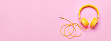 Yellow Headphones On Pink Banner. Minimal Music Concept, Flat Lay, Copy Space