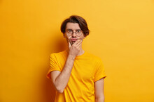 Human Face Expressions Concept. Handsome Adult European Man Holds Chin Pouts Lips Makes Funny Grimace Wears Round Transparent Glasses And Casual T Shirt Isolated Over Yellow Studio Background.