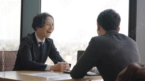 Photo オフィスでミーティングをするビジネスマン