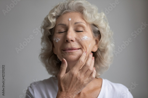 Fotografia, Obraz Relaxed elderly woman with closed eyes taking skincare treatment, applying anti age lotion, moisturizer cream on dry face skin with wrinkles
