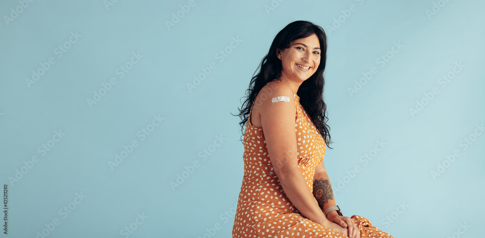 Fototapeta Woman with band-aid on arm after getting vaccine