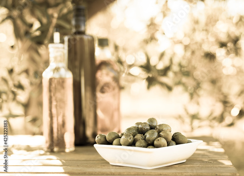 Fotografie, Obraz green olives and oil on table in olive grove