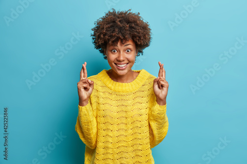 Photo Positive curly haired young woman wears casual yellow sweater crosses fingers for good luck believes dreams come true smiles glad makes wish isolated over blue background