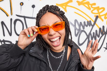 Trendy Cheerful Dark Skinned Hipster Girl Wears Orange Sunglasses Black Jacket Raises Hand Exclaims Loudly Has Cheeky Expression Has Own Fashion Style Poses Against Creative Painted Street Wall