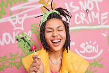 Trendy Cheerful Hipster Girl Smiles Broadly Holds Lollipop Has Fun With Teenagers Of Same Age Wears Yellow Vest Poses Against Colorful Graffiti Wall. Gen Z Generation. Youth Lifestyle Concept