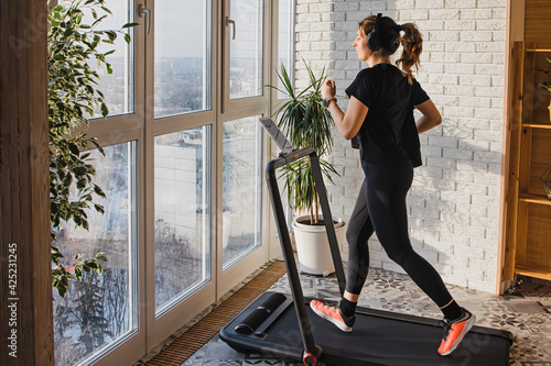 Obraz Woman jogging on the modern compact treadmill at home - fototapety do salonu