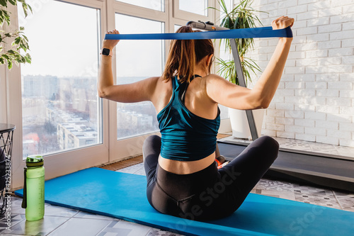 Obraz Young girl doing exercises with resistance band - fototapety do salonu