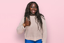 Young African Woman Wearing Wool Winter Sweater Doing Happy Thumbs Up Gesture With Hand. Approving Expression Looking At The Camera Showing Success.
