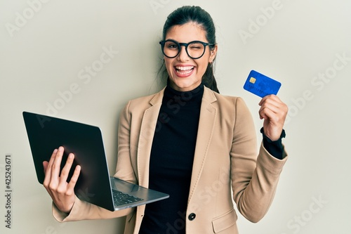 Fototapeta Young hispanic woman wearing business style holding laptop and credit card winking looking at the camera with sexy expression, cheerful and happy face