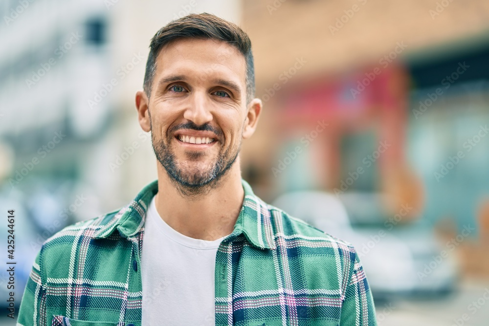Fototapeta Young caucasian man smiling happy standing at the city.