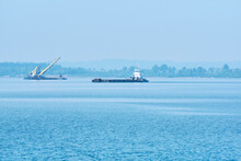 Foggy River Water Landscape With Cargo Barge And Dredger In The Background