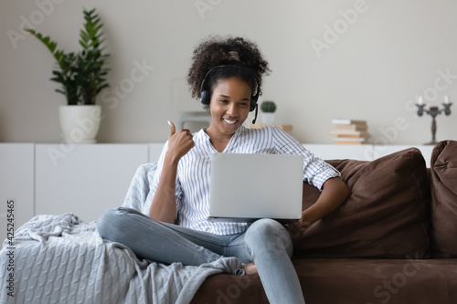 Smiling African American woman in earphones sit on sofa at home talk on video call on laptop. Happy young biracial female in headphones have webcam digital conference. Virtual event concept. - fototapety na wymiar