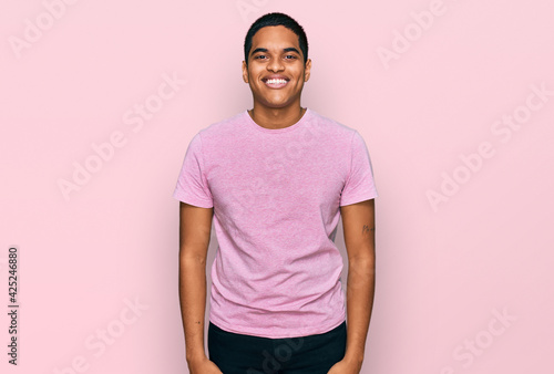 Fotografia, Obraz Young handsome hispanic man wearing casual pink t shirt looking positive and hap