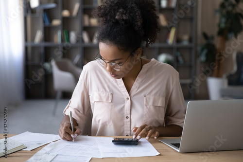 Canvas Print Serious young biracial woman sit at desk manage budget calculate on machine pay bills taxes online on laptop