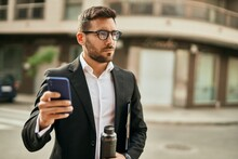 Young Hispanic Businessman With Serious Expression Using Smartphone At The City.