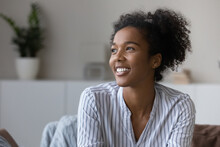 Smiling Millennial African American Woman Relax In Cozy Own Living Room Look In Distance Dreaming Or Visualizing. Happy Young Biracial Female Renter Think Or Plan. Vision, Visualization Concept.